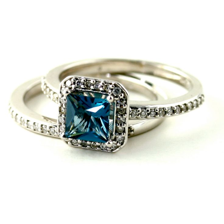 The engagement ring has a 1.10ct Princess cut natural London Blue Topaz at the center, with 44 natural diamonds surrounding it in a beautiful halo and continuing down the ring shank. Gorgeous! Blue Topaz is the birthstone for December.: London Blue Topaz,
