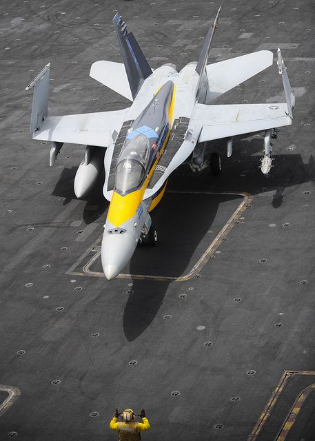 """U.S. 5TH FLEET AOR (Aug. 15, 2013) An F/A-18C Hornet assigned to the """"Blue Diamonds"""" of Strike Fighter Squadron (VFA) 146 is directed across the flight deck of the aircraft carrier USS Nimitz (CVN 68). Nimitz Strike Group is deployed to the U.S. 5"""