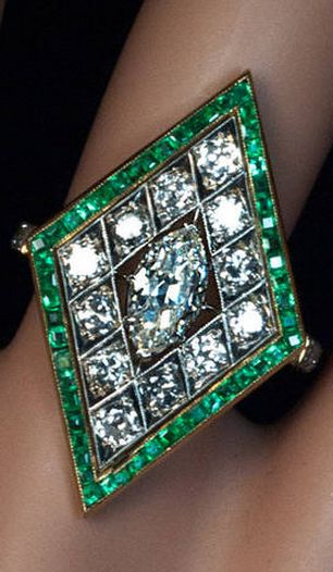 Art Deco Rhombus Shaped Diamond Emerald Gold Ring  1920s The very finely crafted platinum topped 14K gold ring is centered with a prong-set sparkling old marquise cut diamond, framed by 12 bright white old European and transitional cut diamonds, and borde