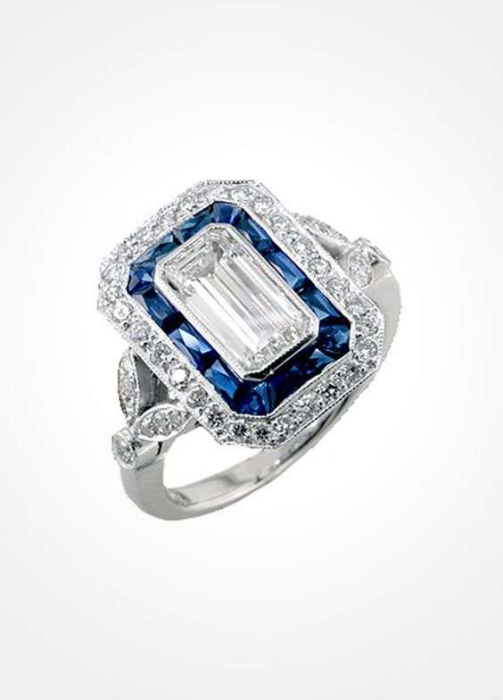The classic emerald cut ring gets a truly unique twist with a halo of sapphire stones that are set securely in platinum.