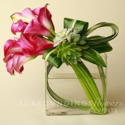 """Something small and modern in glass for the sweetheart table.  """"A modern flower arrangement of callas decorated with lily grass, aspidistra leaves and a cluster of beautiful succulents to add just the right touch. $150.00"""": Aspidistra Leaves, Flor"""