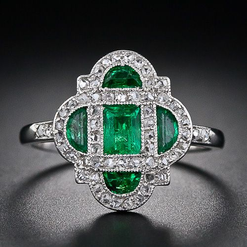 This darling and diminutive early-Art Deco delight - circa 1920 - glistens with a bright green central emerald-cut emerald and four half-moon emeralds lovingly framed in platinum and teeny-tiny rose-cut diamonds. An original and dreamy Art Deco ring - too