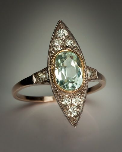 Art Deco Vintage Aquamarine and Diamond Ring  Moscow, circa 1930  The marquise (navette) shaped ring with a millegrain border is centered with an oval aquamarine (approximately 1.53 ct) set in a gold milgrain bezel,   flanked by six old mine and old Europ