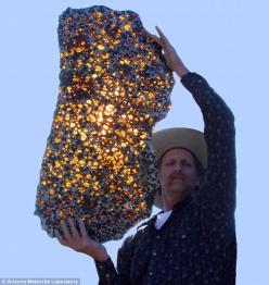 A slice of the Fukang meteorite.  When it slammed into the surface of Earth, there was little sign of the beauty that lay inside. But cutting the Fukang meteorite open yielded a breathtaking sight. Within the rock, translucent golden crystals of a mineral