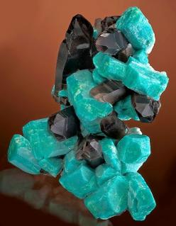 Amazonite crystals with dark Smoky Quartz.. Amazonite is a translucent to opaque feldspar gemstone with a pretty green color. It is the greenish variety of the mineral Microcline. Amazonite is named after the Amazon River of South America. There are no Am
