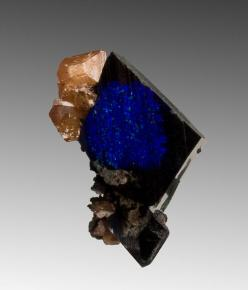 Azurite with Wulfenite'An azurite crystal, sharp-edged with vibrant flashes of blue, has patches where the azurite has pseudomorphed to malachite'Tsumeb Mine, NamibiaI often question myself with 'What the in the world is this mine doing..': Colour