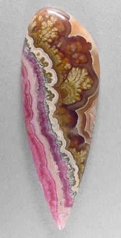 cabochon of rhodochrosite, from Argentina, with PLUMES! At one side, this outstanding stone features wavy bands of glowing pink coloration. And the other side has honey-colored gel (calcite), very gemmy & translucent, which contains several beautifull