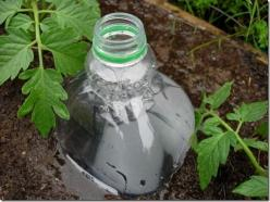 DIY Drip Irrigation System, Made from Plastic Bottles.  The 'system' is super simple. All we have to do is grab some 2-liter plastic bottles, punch 2 holes into the sides and 2 into the bottom, and plant said bottles next to our plants. Fill them