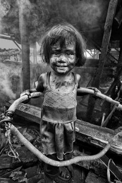 Thomas Tham. It is amazing to me, that this child can smile with the turmoil around her. She picks up a wired conduit to be used as her new found toy. She smiles. She plays. She is a child. Not knowing the world around her disintegrates. Or maybe she does