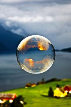 """We went out early one morning and tried to make giant soap bubbles. The sun was rising above the mountain behind us and I managed to capture the sunrise in the reflection of a bubble floating out the fjord.  Captured in Viddal, Norway.""     Camer"