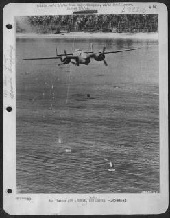 """A B-25 Mitchell from the 405th Bomb Squadron """"Green  Dragons"""", 38th Bomb Group, 5th Air Force doing some low-level  'skip' bombing. The bombers would come in over a target low and fast,  dropping their bombs with delay fuses a distance fro"""