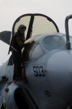 "GULF OF OMAN (July 31, 2013) Aviation Machinist's Mate 3rd Class Andres Mahecha, of San Diego, currently assigned to the ""Gray Wolves"" of Electronic Attack Squadron (VAQ) 142, cleans the canopy of an EA-6B Prowler on the flight deck of the aircraf"