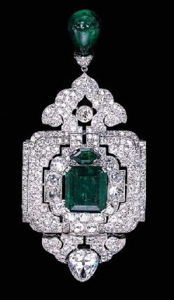 AN IMPRESSIVE EMERALD AND DIAMOND PENDANT/BROOCH, BY CARTIER   Designed as an old European and old mine-cut diamond openwork panel with a central rectangular-cut emerald weighing 12.28 carats, suspending a diamond palmette and emerald bead drop, to the pe