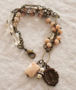 triple-strand bracelet is a mix of cut glass rose beads, vintage pearls, an oversized Peach Aventurine bead, faceted chuncky Citrine, faceted Pineapple Quartz ovals, Peach Aventurine rounds, a vintage Miraculous Medal of Mary and wonderful old rhinestone