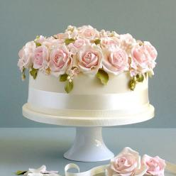 Brides.com: Wedding-Worthy One-Tier Cakes. A White Wedding Cake Topped with Pink Roses. Pink roses, a classic wedding flower, are the perfect topper for this lovely Made With Love cake. The elegant design is a splendid choice for a traditional wedding.  S