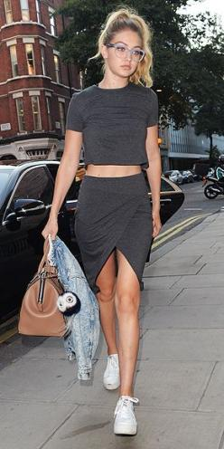 Gigi Hadid in a dark gray wrap skirt and crop top by Twenty, Ash white sneakers, and Miu Miu glasses: Wrap Skirts, Celebrity Style, Crop Tops, Gigihadid, Street Style, Gigi Hadid Outfit, White Sneakers