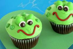 Frog Cupcakes - 1 box (18.25 oz.) chocolate cake mix 1 ½ cans (16 oz. each) vanilla frosting 1 tube (6 oz.) red decorating icing Green food coloring ⅓ cup M&M'S® Brand MINIS® Milk Chocolate Candies 48 pieces M&M'S® Brand Peanut Chocolate Candies 2