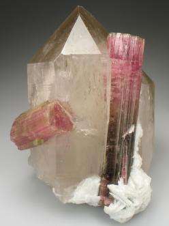 Tourmaline on Smoky Quartz    Smoky Quartz emits a high level of energy. It helps ground the holder with Earth energies and is good for working with the Root Chakra.  Use Smoky Quartz to absorb and transmute negative energy. While this stone has a slow an