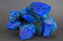 Chalcanthite: Its name derives from the Greek words chalkos and anthos, meaning copper flower, is a richly-colored blue/green water-soluble sulfate mineral. It is commonly found in the late-stage oxidation zones of copper deposits. Due to its ready solubi
