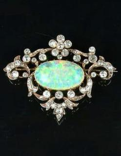 An opal and diamond brooch/pendant, circa 1900, the central opal cabochon, to an openwork cartouche-shaped border of scrolling flowers and foliage set with old brilliant and single-cut diamonds, width 4.4cm.