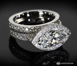 This stunning 2 carat maquise cut diamond is accented by a diamond halo and a antique style pave band.