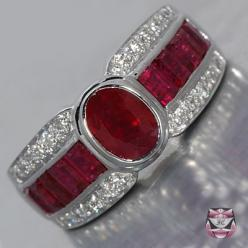This Art Deco style Ruby Ring is of considerable weight and presence, measuring 9mm wide and 6.5mm deep and is constructed in 18k white gold. Weighing 7.8g and collectively mounted with 4.04cts of oval and baguette rubies graded 'lively crimson' c