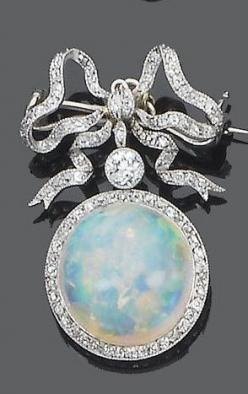 A belle époque opal and diamond brooch, circa 1905. The single-cut diamond tied ribbon bow suspending an old brilliant-cut diamond and a circular cabochon opal with a single-cut diamond border, mounted in silver and gold, detachable brooch fitting.