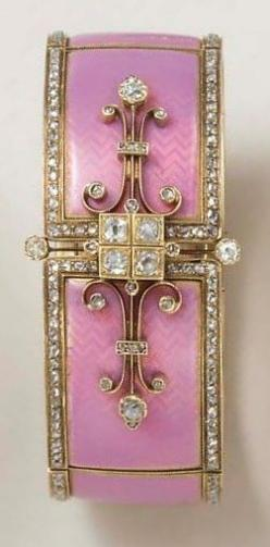 AN ANTIQUE ENAMEL AND DIAMOND BANGLE BRACELET. Of articulated design, the pink opalescent guilloché enamel panels with rose-cut diamond borders, joined by a central old European-cut diamond four-stone plaque, flanked on either side by scrolled knife-edge