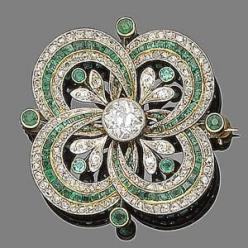 An emerald and diamond brooch/pendant, ca 1915. Centrally-set with an old brilliant-cut diamond within an openwork quatrefoil set with alternating rows of calibré-cut emeralds and rose-cut diamonds, accented with circular-cut emerald and single-cut diamon