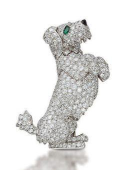 "AN UNUSUAL DIAMOND DOG BROOCH, BY CARTIER . They describe the pin: ""Designed as an articulated begging terrier with emerald eyes and onyx nose, a mechanism on the reverse allows the paw and tail to move, 4.2 cm, with French assay mark for platinum and"