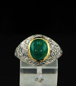 Antique Deco emerald and diamond ring in elegant domed design    The front panel is richly set by old cut diamonds in adorable pattern of foliate design  surrounding the centre large cabochon cut emerald set into rub over frame    Carved details edging th
