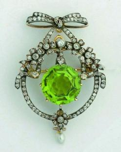 Belle Epoque diamond and peridot brooch, centrally claw set with a round cut peridot (10.17cts), encircled by an old and mixed cut diamond encrusted panel detailed with flowers and leaves below a diamond set bow and ribbon, accented with a pearl drop, all