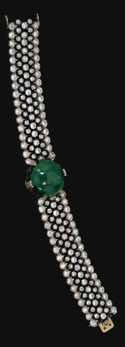 EMERALD AND DIAMOND BRACELET,  CIRCA 1915.  Centring on a circular cabochon emerald highlighted with circular- and single-cut diamond set motifs, to an articulated wide band designed as an open work mesh collet-set with circular-cut diamonds, within a mil