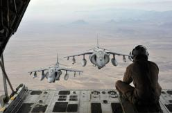 U.S. Marine Corps Cpl. Gregory Moore, combat videographer with 3rd Marine Aircraft Wing, sits on the back of a KC-130J Hercules to capture imagery of AV-8B Harriers flying over mountains in Helmand province, on December 6, 2012. (USMC/Staff Sgt. Loobens A