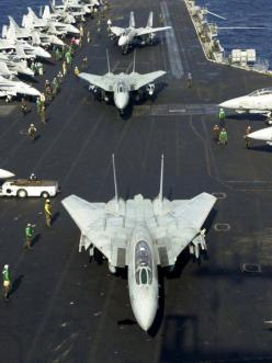 F14 Tomcat jets lining up for take off aboard aircraft carrier.