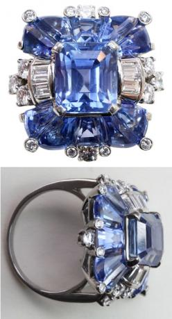 A fabulous platinum ring set with natural pastel colored Ceylon sapphires; the center an emerald cut sapphire flanked by special modified trapezoid cut sapphires, all in exactly the same color and accented by baguette and brilliant cut diamonds, signed an