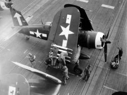 "A BUNKER HILL F4U Corsair is readied for strikes on 16 February 1945. 5-inch HVAR ""Holy Moses"" rockets are loaded and armed under the wings. -U.S. Navy photo in NARA record group 80-G"