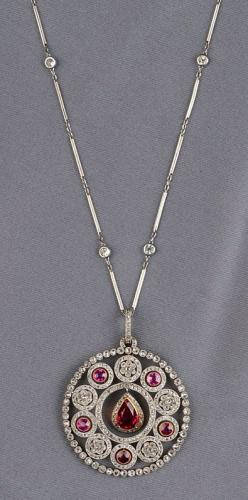 Edwardian Synthetic Ruby, Ruby, and Diamond Pendant, Retailed by Koch, centering a pear-shaped synthetic ruby measuring approx. 9.00 x 5.40 x 3.90 mm, set in a flexible mount framed by rose-cut diamond melee, further set with circular-cut rubies and rose-