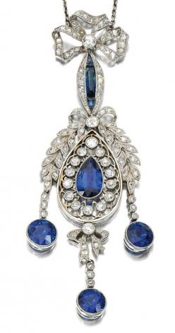 SAPPHIRE AND DIAMOND PENDANT, 1910S.  The millegrain open work pendant set with circular-cut and rose diamonds, suspending three circular-cut sapphire drops, to a ribbon bow surmount and trace link chain, length approximately 400mm, fitted case.