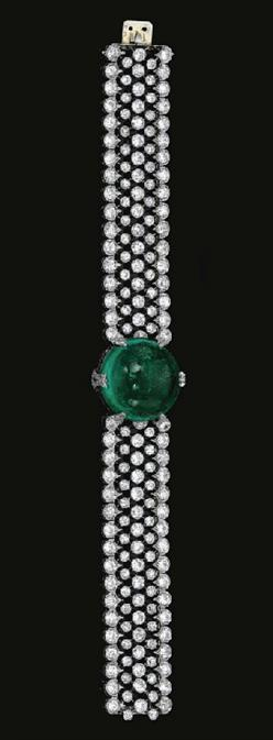 FINE  EMERALD  AND  DIAMOND  BRACELET,  CIRCA  1915	  	  Centring  on  a  circular  cabochon  emerald  highlighted  with  circular-  and  single-cut  diamond  set  motifs,  to  an  articulated  wide  band  designed  as  an  open  work  mesh  collet-set  w