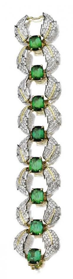 TOURMALINE AND DIAMOND BRACELET, SCHLUMBERGER, TIFFANY & CO.  Set with a row of 8 cushion-shaped green tourmalines within a border of curving leaves, pavé-set with 480 round diamonds weighing approximately 9.50 carats, mounted in platinum and 18 karat