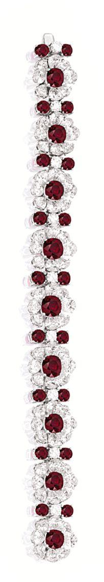 VERY FINE RUBY AND DIAMOND BRACELET. Set with nine graduated cushion-shaped rubies together weighing 18.47 carats, each surrounded by pear-shaped diamonds, embellished by eighteen oval rubies and brilliant-cut diamonds, the rubies and diamonds together we