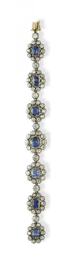 A SET OF ANTIQUE SAPPHIRE AND DIAMOND JEWELLERY   Comprising a necklace set with a line of sixteen oval and cushion-shaped sapphires, each within an old-cut diamond cluster, linked by diamond collets, a bracelet en suite, mounted in silver and gold, circa