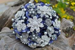 This bouquet features silver and pearl rhinestone jewelry with some pearls and faceted glass beads wired in. The filler flowers are a deep blue and I've added swarovski rhinestones to the petals. The bouquet is finished with a blue ribbon, which can b