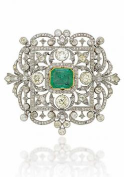 AN EARLY 20TH CENTURY EMERALD AND DIAMOND BROOCH/PENDANT The curved openwork cartouche shaped panel with central rectangular cut-cornered emerald within an old-cut diamond border, to the similarly-set scrolling foliate surround with four circular-cut diam