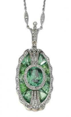 DEMANTOID GARNET AND DIAMOND PENDANT, CIRCA 1910, COMPOSITE. Set with an oval demantoid garnet within a surround of calibré-cut similar stones, the borders set with rose-cut diamonds, to a later trace link chain, length approximately 400mm, signed Tiffany