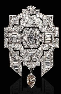 A COLORED AND NEAR COLORLESS DIAMOND BROOCH   The openwork pavé-set diamond plaque centering upon a navette-shaped diamond, enhanced by baguette and triangular-cut diamonds, suspending a detachable brown marquise diamond, mounted in platinum and 18K white