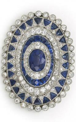 An art deco sapphire and diamond brooch, circa 1925 centering an oval-shaped sapphire framed with several successive rows of old European and single-cut diamonds and calibré and triangular-cut sapphires; central sapphire weighing approximately: 2.50 carat