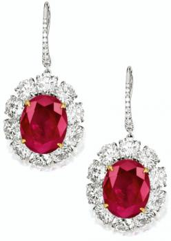 PAIR OF RUBY AND DIAMOND PENDENT EARRINGS    Each suspending on an oval ruby weighing 12.17 and 10.46 carats respectively, surrounded by brilliant-cut diamonds extending to the hook surmount, the diamonds altogether weighing approximately 11.05 carats, mo