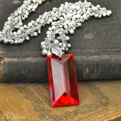 62 carat red topaz baguette is concave faceted & dangles at the bottom of a sterling silver cluster chain